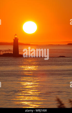 Ram Island Ledge Lighthouse with a sunrise reflecting off the ocean water, Portland, Maine. - Stock Photo