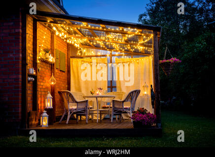 View over cozy outdoor terrace with table and chairs, very romantic lighting, white lanterns, candles burning, led string party lights and bulbs with - Stock Photo