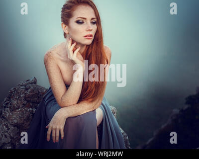Summer outdoors portrait of beautiful furious scandinavian warrior ginger woman in grey dress with metal chain mail. High in the mountains, fog and my - Stock Photo
