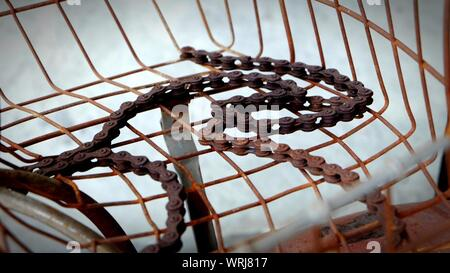Old Bicycle Chain On Rusty Metal Grid - Stock Photo