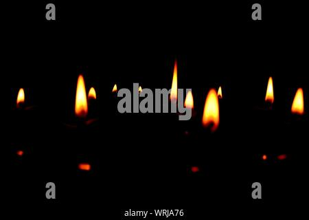 Lit Diwali Oil Lamps Against Black Background - Stock Photo