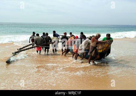 Koggala, Sri Lanka, Dec 03, 2018 fishermen pushing the boat on the sea. - Stock Photo
