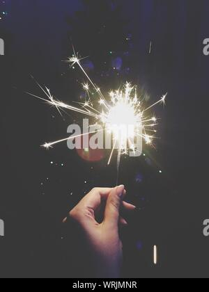 Close-up Of Hand Holding Diwali Cracker Against Black Background - Stock Photo