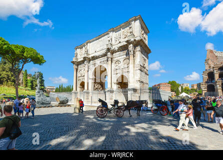 A horse drawn carriage and driver wait by the Arch of Constantine near the Forum as tourists pass by the famous landmark in Rome, Italy - Stock Photo