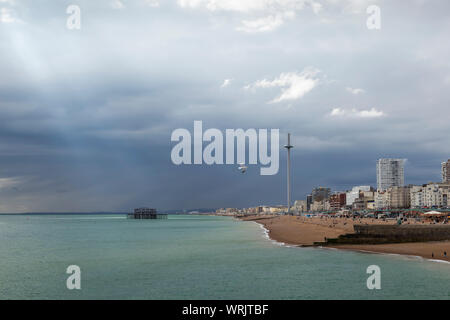 light shining through the clouds on brighton seafront - Stock Photo