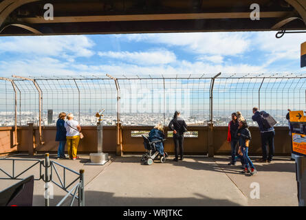 Tourists including a women in a wheelchair enjoy the view from the first platform of the Eiffel Tower on a sunny day in Paris France - Stock Photo