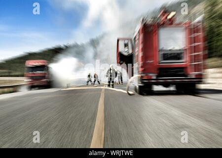 Blurred Motion Of Firefighters Spraying Water On Burning Truck - Stock Photo