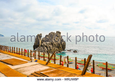 Umbrellas line the sandy beach of the Spiaggia di Fegina close to the large rock at the village of Monterosso al Mare Italy, part of the Cinque Terre - Stock Photo