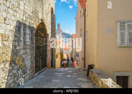Tourists enjoy a meal at a sidewalk cafe on one of the narrow alleys inside the ancient walled city of Dubrovnik, Croatia. - Stock Photo