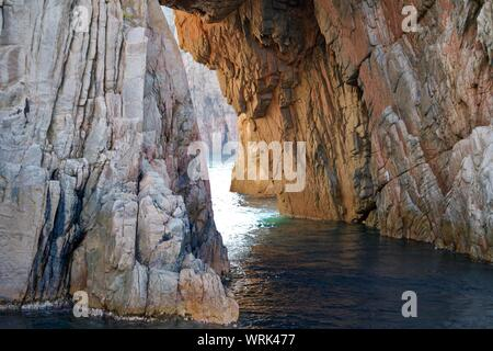 opening between two rough cliffs in the turquoise ocean - Stock Photo