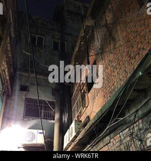 Low Angle View Of Electrical Cables Hanging Outside Old Building With Air Conditioner Condenser Units On Building Wall - Stock Photo