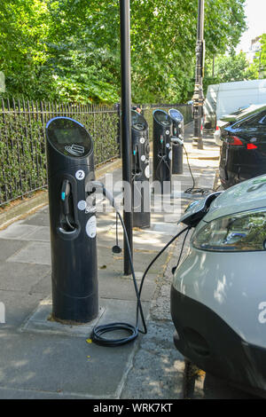 LONDON, ENGLAND - JULY 2018:  Care plugged into a charging point for electric cars kerb-side on a street in central London - Stock Photo