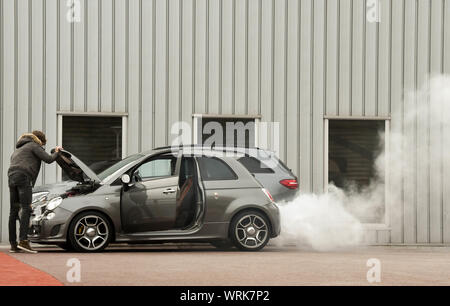 MONACO,EUROPE - JANUARY 2018: A driver looking at the engine of a car with white smoke blowing from the exhaust - Stock Photo