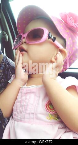 Close-up Of Baby Girl Wearing Sunglasses While Traveling In Car - Stock Photo