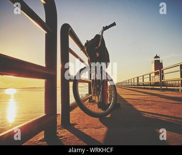 Bicycle Parked On Pier By Lake During Sunset - Stock Photo