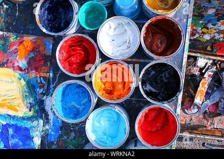 Directly Above Shot Of Multi Colored Painting Cans On Table - Stock Photo