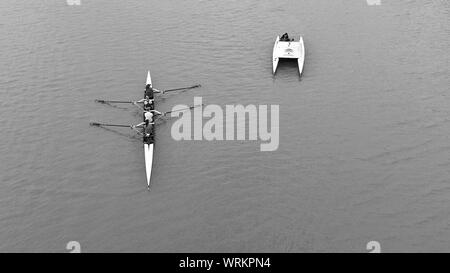 People Rowing In Racing Shell - Stock Photo