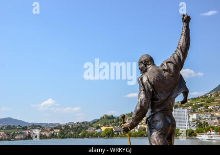 Montreux, Switzerland - July 26, 2019: Famous statue of Freddie Mercury, singer of the famous band Queen. City by Lake Geneva in background. Popular tourist attraction. Copy space, a place for text. - Stock Photo