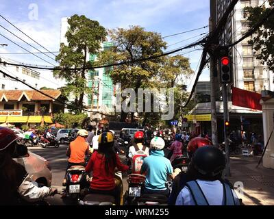 People On Vehicles Waiting At Red Light Signal By Road - Stock Photo
