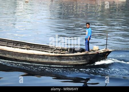 High Angle View Of Fisherman Standing On Boat Sailing On River