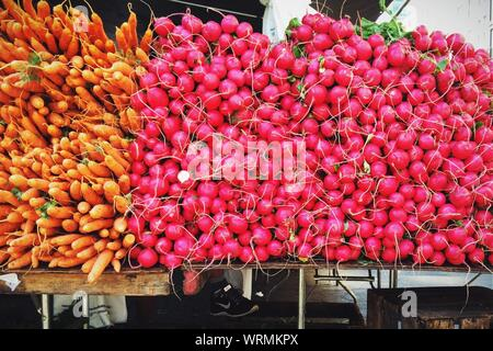 Heaps Of Carrots And Radishes On Table For Sale - Stock Photo