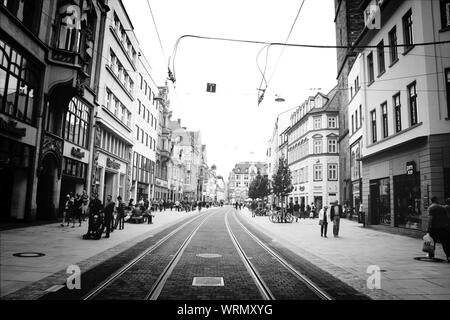 People Walking On Street Along Buildings - Stock Photo