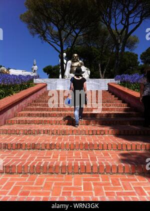 Rear View Of Woman On Steps Walking Towards Statues At Bacalhoa Buddha Eden - Stock Photo