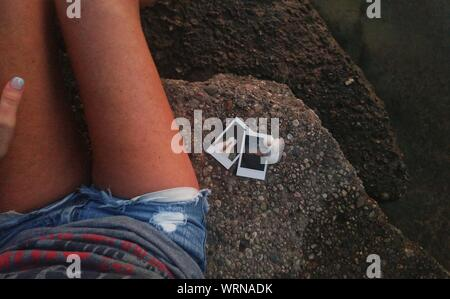 Midsection Of Young Woman Sitting With Photographs On Rocks - Stock Photo