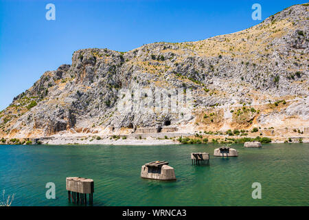Old broken fragments of bridge over river Drini, Albania - Stock Photo