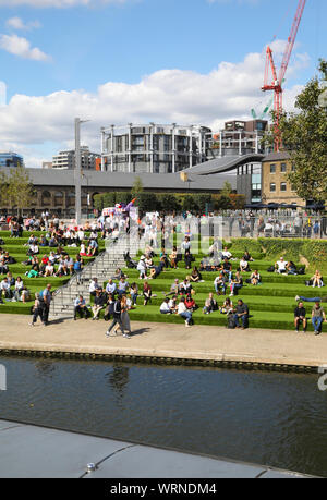 The grass steps leading down from Granary Square to Regents Canal at Kings Cross, NC1, in the autumn sunshine, in north London, UK - Stock Photo