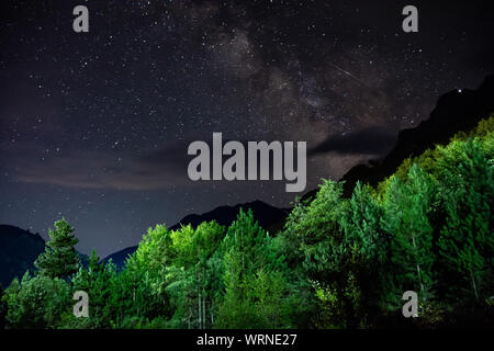 Milky Way with falling star above mountain peaks in National Park Valbona in Albania, Europe - Stock Photo