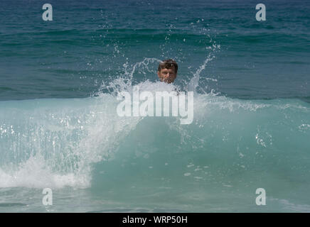Shirtless Man By Waves In Sea At Beach - Stock Photo