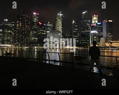 Silhouette Man Looking At Illuminated Skyline From Marina Bay Sands Boardwalk At Night - Stock Photo