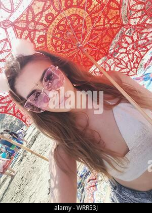 Portrait Of Beautiful Woman Wearing Sunglasses While Holding Umbrella - Stock Photo