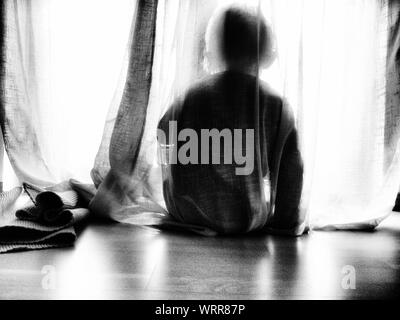 Rear View Of Child Hiding Behind Curtain - Stock Photo