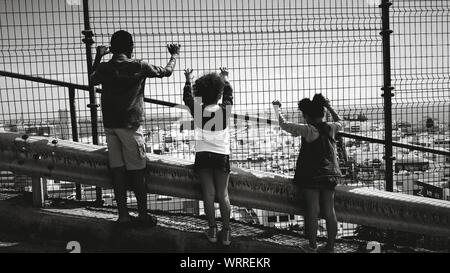 Rear View Full Length Of Siblings Looking At Townscape Through Chainlink Fence - Stock Photo