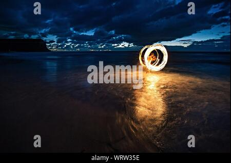 Person With Illuminated Wire Wool On Shore - Stock Photo