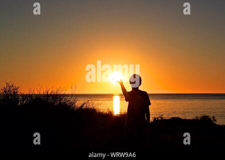 Boy Cupping Hand Under Sun - Stock Photo