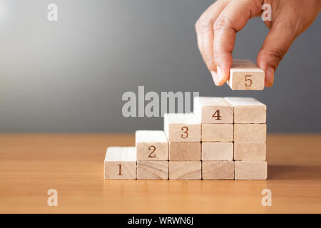 Women hand putting a wooden block on top and arranging wooden blocks stacking on wooden table  in the shape of a staircase, Business concept for growt - Stock Photo