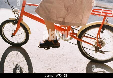 Low Section Of Woman Riding Bicycle - Stock Photo