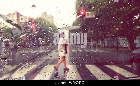 Woman Crossing Road Seen Through Wet Windshield Of Car In Rain - Stock Photo