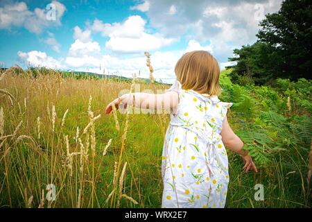 Rear View Of Girl Wearing White Floral Dress On Field Against Sky - Stock Photo