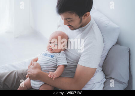 asian father with his son playing together