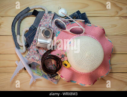 Stack of clothes and travel accessory on wooden plank. Travel concept. - Stock Photo
