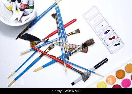 High Angle View Of Watercolor Paints And Brushes On Table