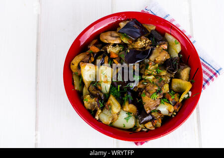 Vegetable saute with eggplants in ceramic bowl on white wooden table. Studio Photo - Stock Photo