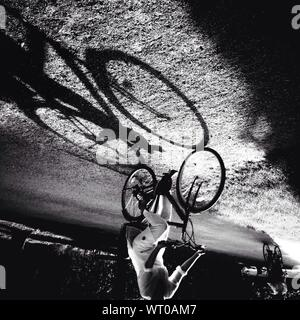 Low Section Of Woman Riding Bicycle In Park - Stock Photo