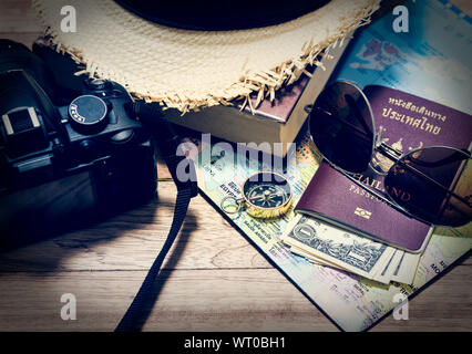 Travel concept with digital camera, straw hat, book, map, compass, passport, money and sunglasses on wooden table - Stock Photo