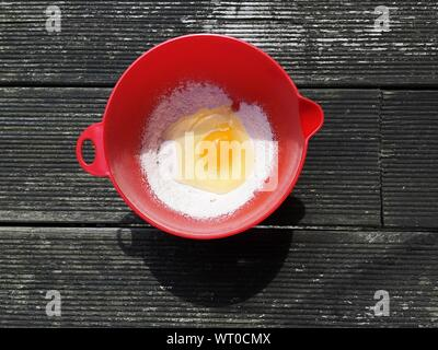 Directly Above View Of Egg Yolk And Flour In Bowl On Table - Stock Photo