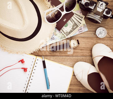 Travel concept with digital camera, straw hat, sunglasses, world map, compass, passport, money, wristwatch, earphones, shoes, notepad and pen on woode - Stock Photo
